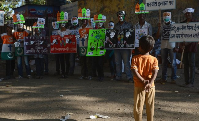 A child watches as Indian students assemble for a peace rally on the 65th death anniversary...