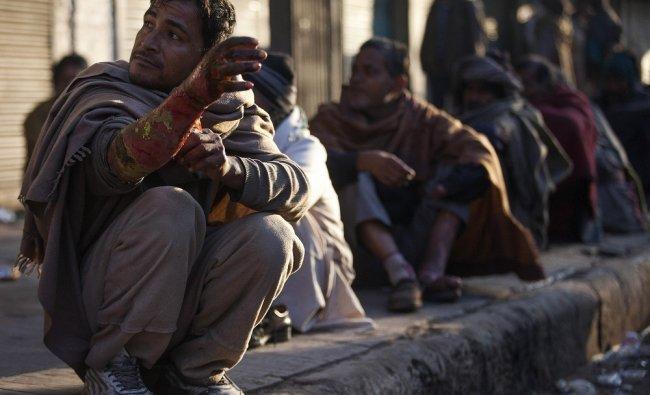 Homeless people wait for treatment on the Indian roads