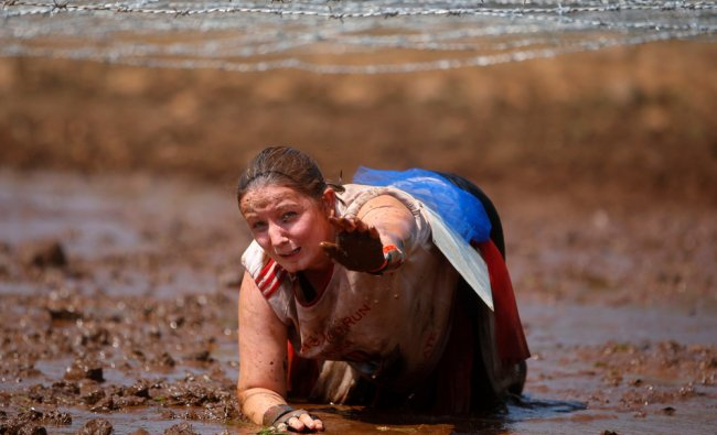A competitor reaches out her hand after falling as she tries to crawl through a mud trap under...