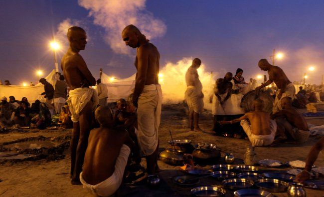 Indian devotees prepare food as they wait for day break to take a holy dip at Sangam...