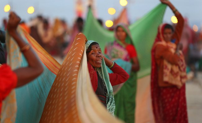 Indian Hindu devotees dry their cloths after a holy dip at Sangam, at the confluence of the Rivers..