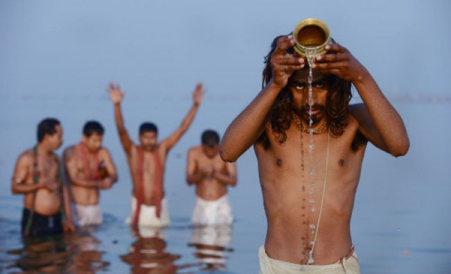 TOPSHOTS Hindu devotees pray as they bathe in the Sangam or confluence of the Yamuna, Ganges...