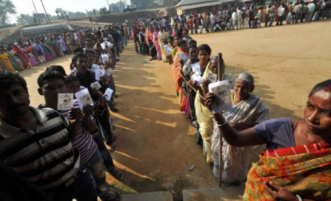 People shows voter identity cards as they stand in a queue to cast their vote