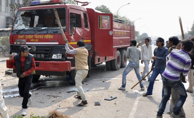 Protesters damage a fire engine during a strike in Noida...