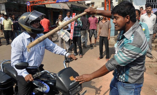 A Indian demonstrator wields a stick after stopping a motorcyclist during a two-day strike...