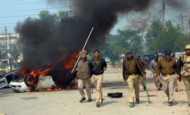 Policemen chase protesters as they walk past a vehicle sent of fire by the protestors during a bandh