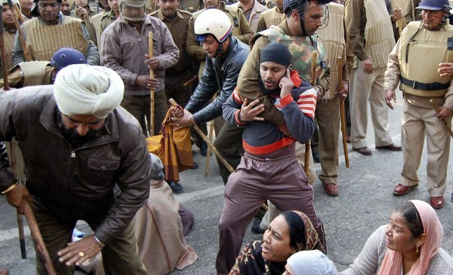 Policemen move suatting protestors during first day of two-day nationwide strike in Ambala...