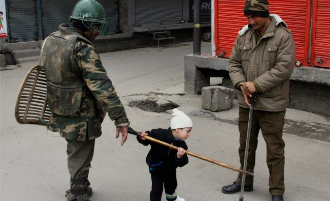 A child plays with the stick of a security personnal as they stand guard during second day of strike