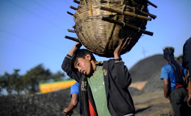A young worker carries a stack of baskets used to load coal into trucks at a road side coal depot...