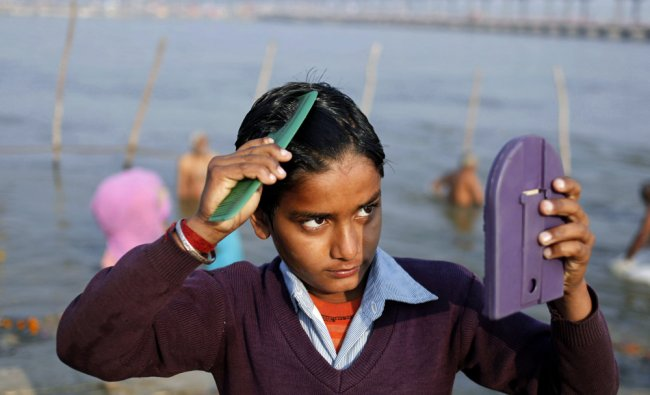 A young Hindu devotee combs his hair after a dip at the Sangam...