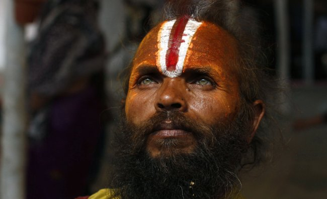 A Hindu holy man pauses as he returns after taking part in a community feast at the Ashram...