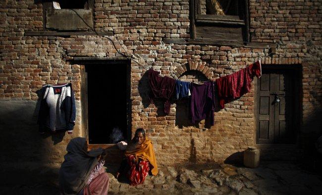 A woman smokes a cigarette outside her house at Khokana in Lalitpur.