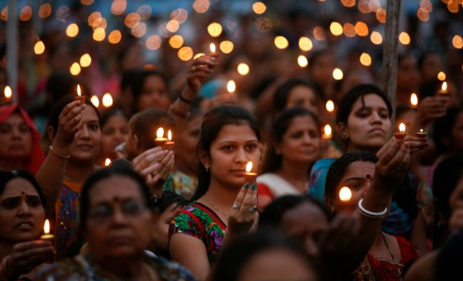 People hold lamps as they pray to the Hindu god Vishwakarma to celebrate his birthday at a temple...