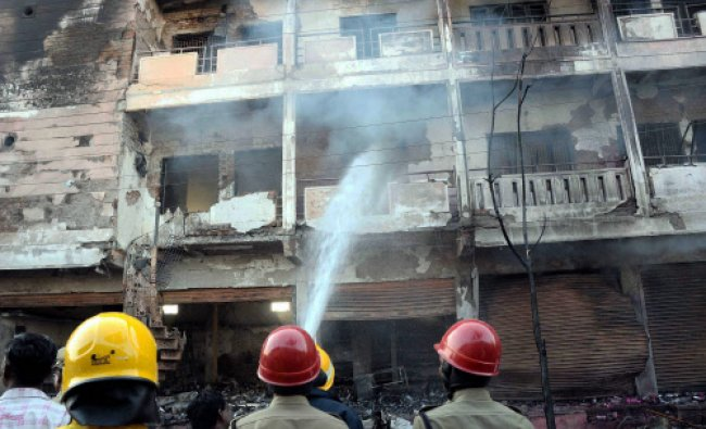 Fire fighters douse fire after a portion of a wall collapsed following a gas cylinder blast...