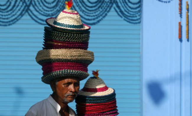 A vendor wears a stack of hats as he waits for customers along a roadside in Kolkata...
