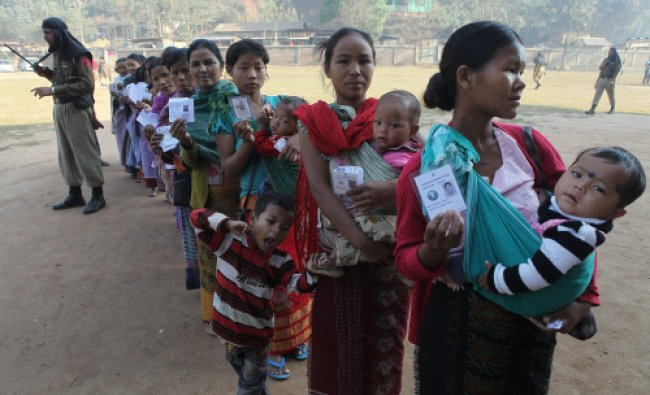 Indian women carry their babies and display their identity cards as they stand in queue...