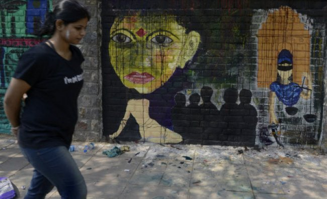 An Indian artist walk past wall paintings created during the \'Design The Change\' wall art event...