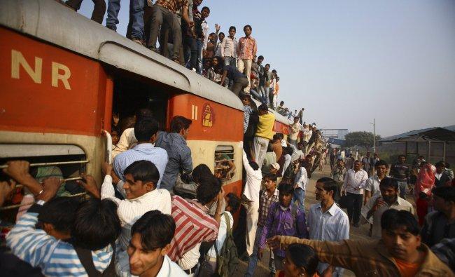 Commuters struggle to board a train at Noli railway station in Uttar Pradesh...