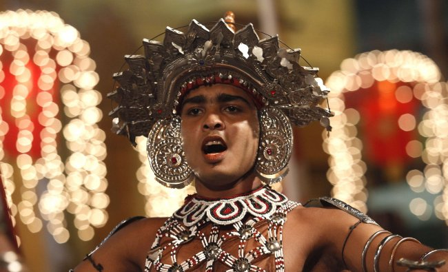A traditional dancer from Sri Lanka performs at Navam Perahera, a Buddhist pageant of elephants...