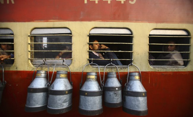 Empty milk containers hang from the window of a train in Uttar Pradesh...