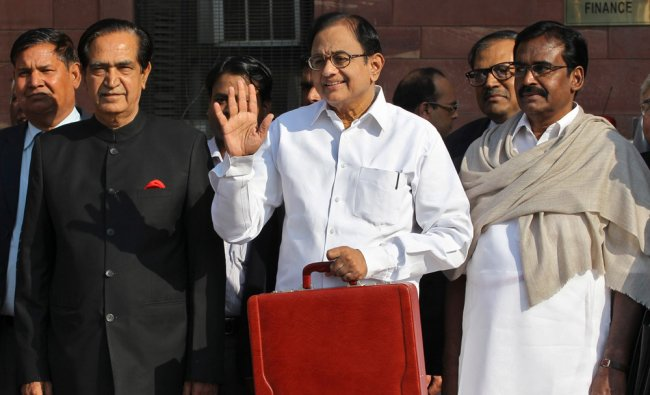 India\'s Finance Minister Palaniappan Chidambaram (C) poses as he leaves his office to present the...