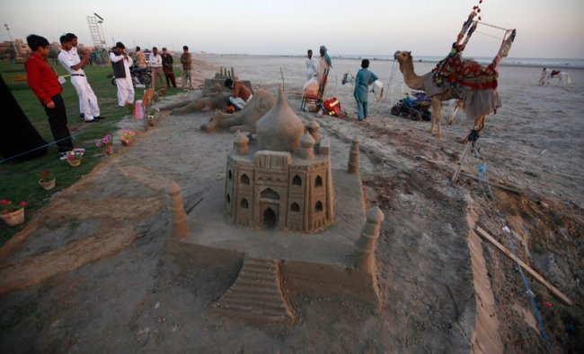 People stand near sand artist Arif, 23, as he applies the final touches to a sand sculpture ...