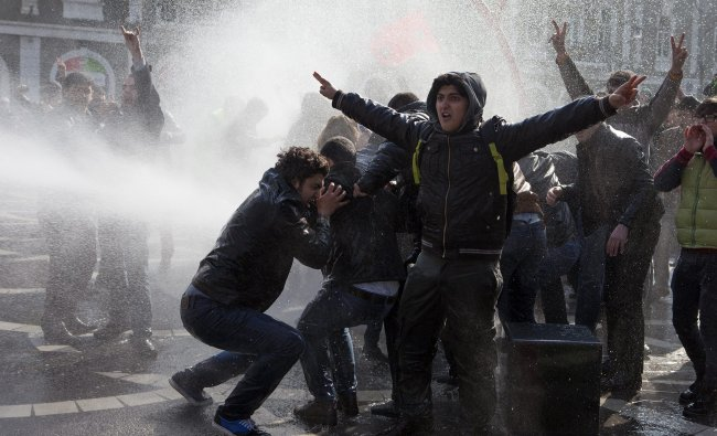 Policemen use water cannons to break up the crowd of protesters during a rally in Baku