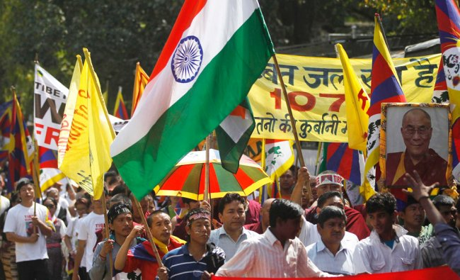 Tibetan Exiles in India carry an Indian flag and a portrait of their leader the Dalai Lama ...