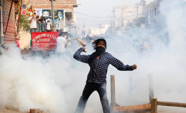 A Pakistani Christian throws a tear-gas canister to the police during a protest ...
