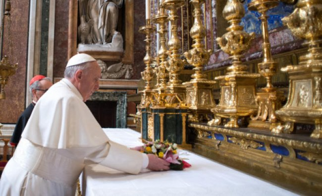 In this photo provided by the Vatican newspaper L\'Osservatore Romano, Pope Francis puts flowers...