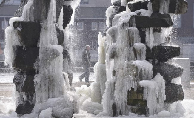 A man passes a frozen fountain in Duisburg, western Germany, Thursday, March 14, 2013...