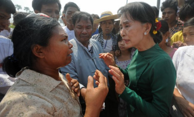 Myanmar democracy leader Aung San Suu Kyi (R) speaks with a woman during her visit at a village...