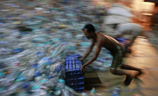 A man collects empty plastic bottles to be recycled at a factory in a slum in Mumbai March 15...