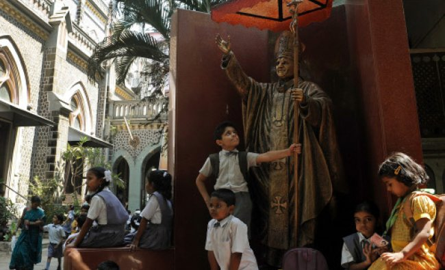Schoolchildren play near the statue of late Pope John Paul II at the Holy Name Cathedral in Mumbai..