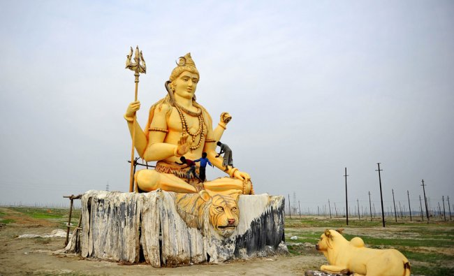 Children play on a giant statue of Hindu god Lord Shiva near the Sangam in Allahabad...