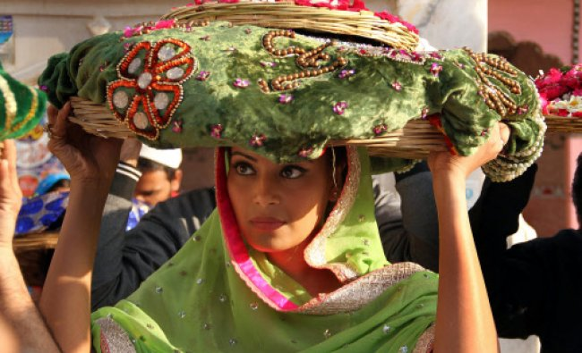 Bollywood actress Bipasha Basu carries offerings of velvet cloth and flowers at the shrine of Sufi..