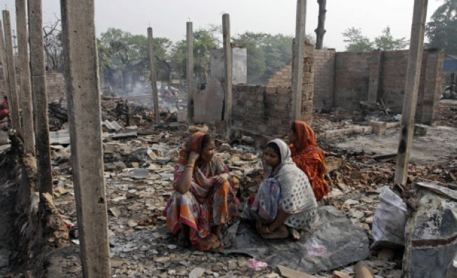 Women sit amidst the remains of their shanties after it caught fire early morning on the outskirts..
