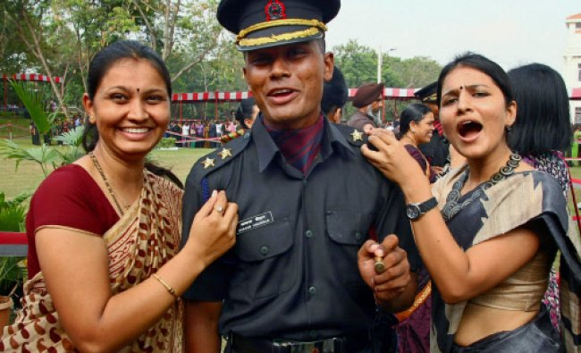 A cadet jubilates with his family members after a passing out parade at Officers Training...