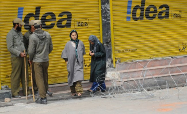 Kashmiri women walk past policemen standing guard during the third day of a curfew imposed...