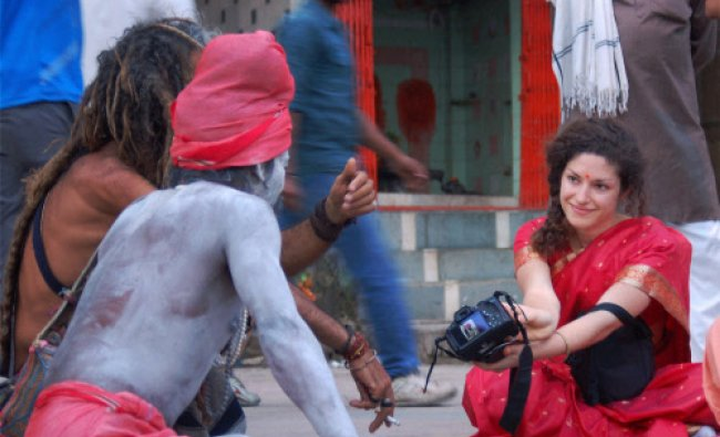 A foreign tourist showing pictures to sadhus in her camera in Varanasi on Saturday...