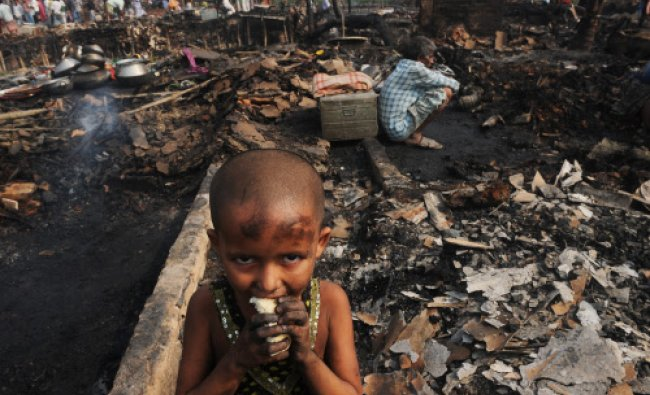An young slum dweller eats bread standing near gutted shanties in the Santoshpur area on the...