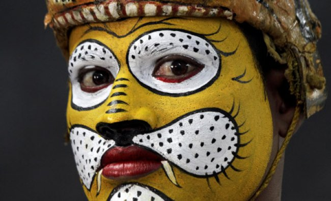 A traditional tiger dancer from Orissa state waits to perform during a Save Our Tigers awareness...