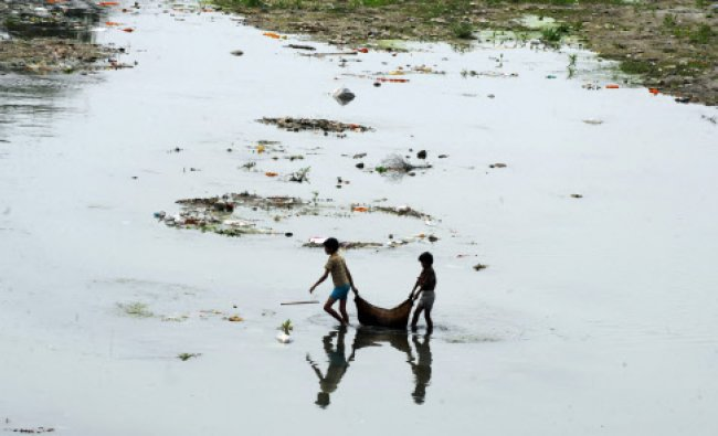 Children carry recyclable items from the polluted water of the Mahananda river in Siliguri...