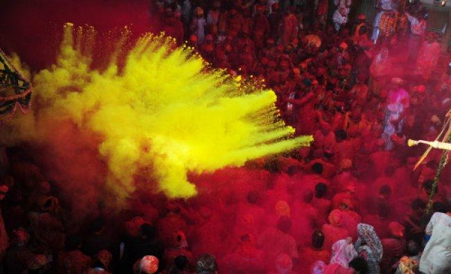 Devotees throw coloured powder at the Radha Rani temple during the Lathmar Holi festival...
