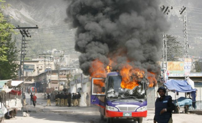 A policeman stands near a bus set ablaze by angry protesters during a demonstration against power...