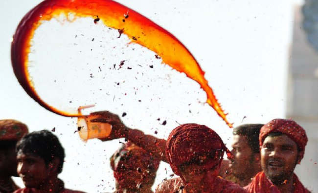 Devotees throw coloured water at the Radha Rani temple during the Lathmar Holi festival in Barsana..