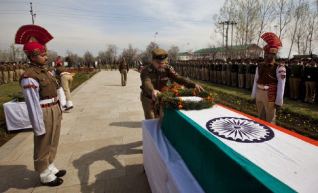 An Indian Border Security Force (BSF) officer lays a wreath on the coffin of his colleague...