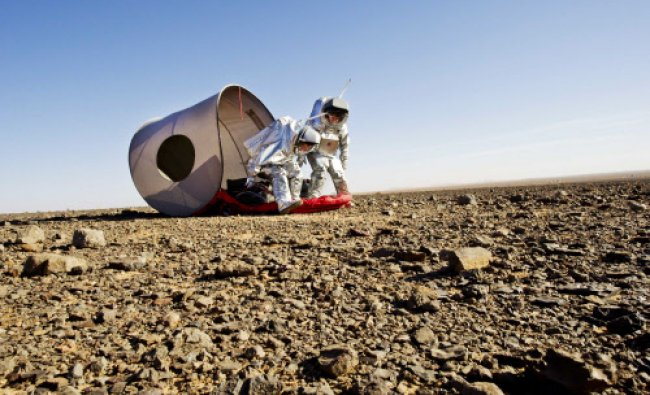 Scientists wearing Aouda Mars space suit simulators while testing the deployable shelter...