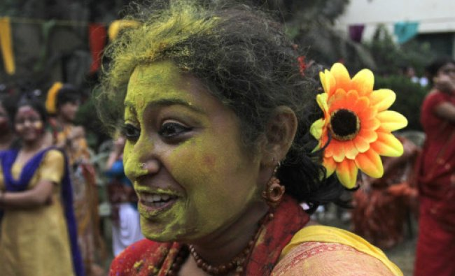 Students smear each other\'s faces with colored powder as they celebrate Holi, the festival of...