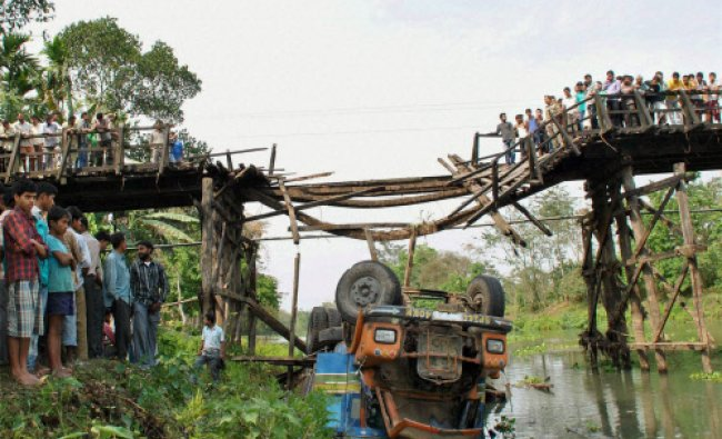 Local residents look at a truck that fell into a stream after collapse of a wooden bridge in Nagaon.